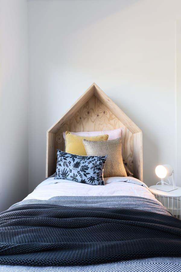 逗人喜爱的木帐篷样式木bedhead在一张被称呼的儿童` s床上 库存图片