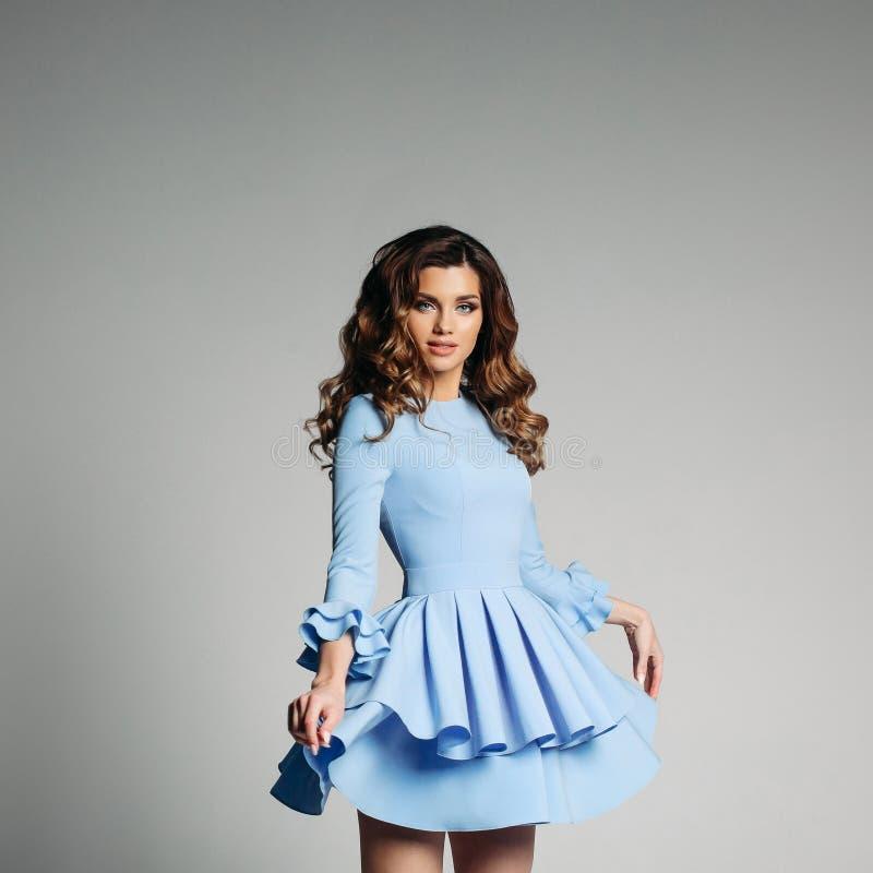 逗人喜爱的浅兰的礼服的可爱的夫人有装饰衣裙的 免版税库存图片