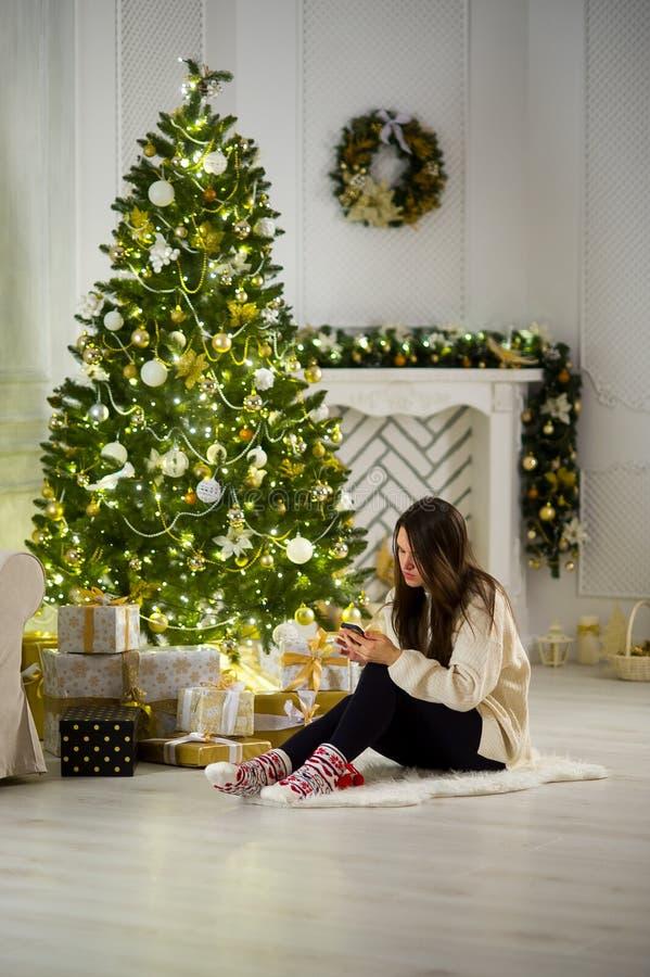 逗人喜爱的深色头发的女孩在与手机的圣诞树附近坐在手上 库存照片