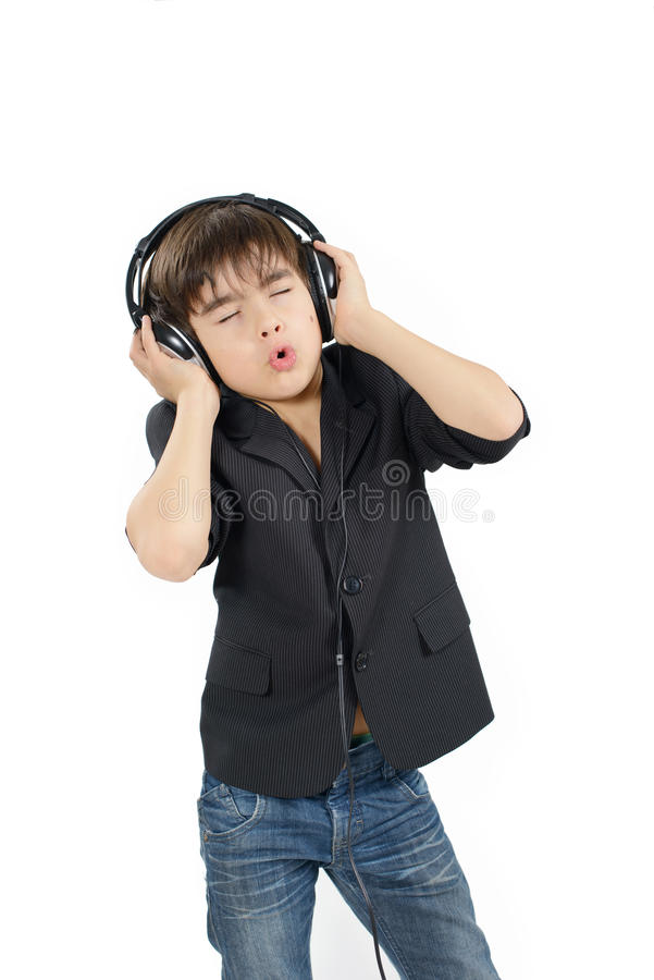 逗人喜爱的深色头发的男孩听到在耳机的音乐 图库摄影