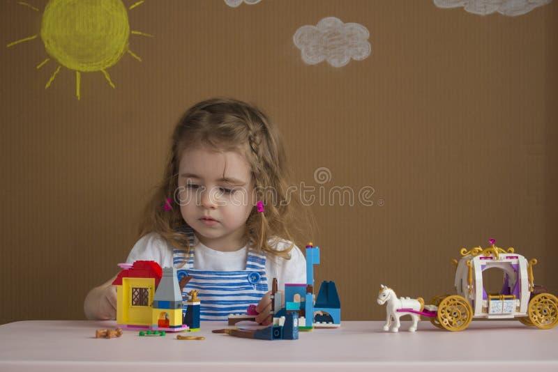 逗人喜爱的滑稽的使用与建筑玩具的学龄前儿童小女孩在幼儿园屋子里阻拦建造塔 免版税库存照片