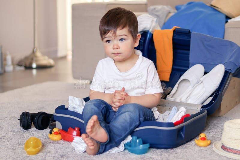 逗人喜爱的滑稽的矮小的男婴有siiting的休息在蓝色手提箱疲乏对包装的衣裳和玩具为假期 免版税库存图片