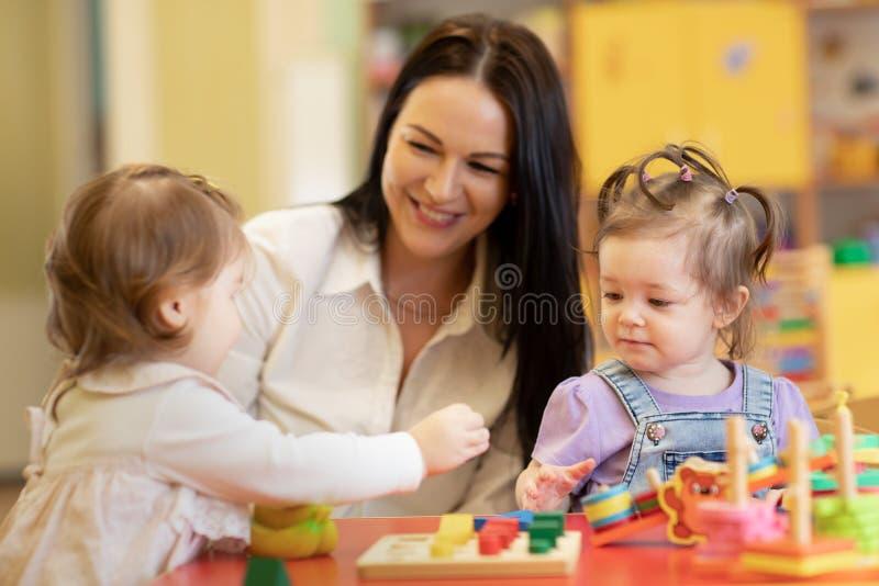 逗人喜爱的演奏教育玩具的妇女和孩子在幼儿园或托儿所室 免版税库存图片