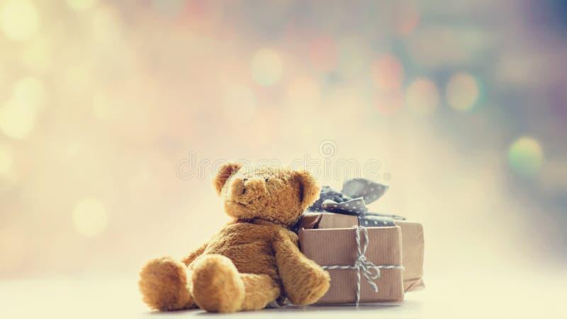 逗人喜爱的玩具熊和美丽的礼物在彩色小灯bokeh ba 免版税库存照片