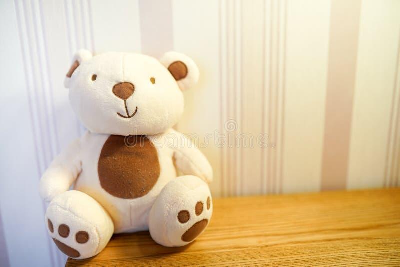 逗人喜爱的玩具熊在木桌上的一个儿童居室 免版税图库摄影