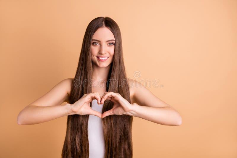 逗人喜爱的甜逗人喜爱的夫人画象做心脏想要日期展示爱男朋友有做法光滑的柔滑的发型打扮 免版税图库摄影