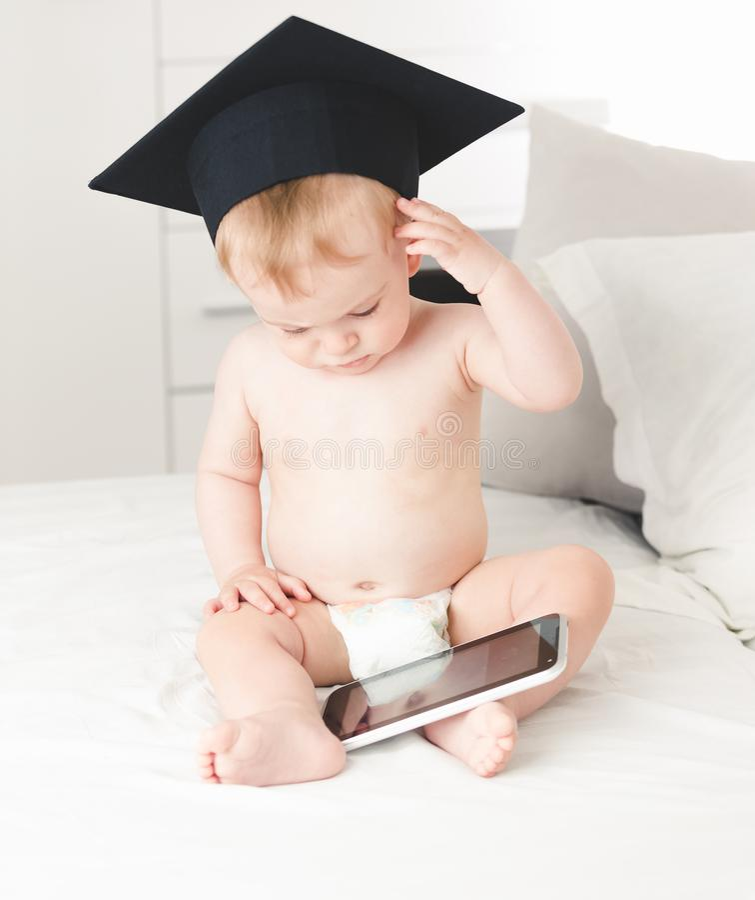 逗人喜爱的男婴佩带的教授帽子摩擦前额被定调子的画象,当使用数字式片剂时 图库摄影