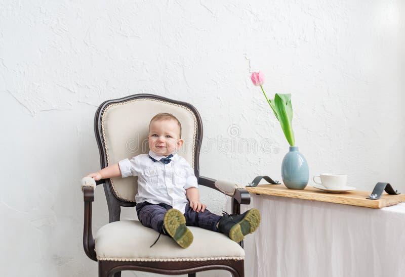 逗人喜爱的男婴在穿时髦的衣裳的1岁以下坐在葡萄酒椅子在本级教室 免版税库存照片