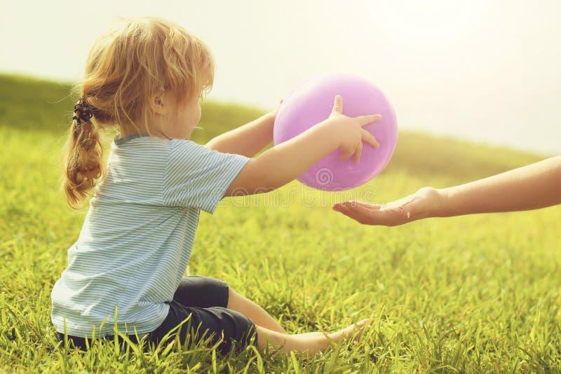 逗人喜爱的男婴给紫罗兰色玩具气球 库存图片