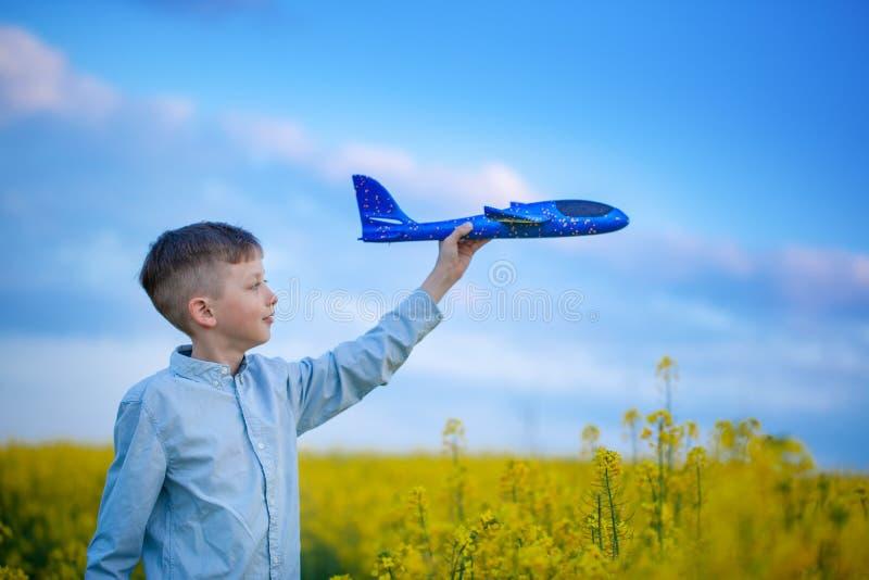 逗人喜爱的男孩使用与在旅行天空蔚蓝和梦想的一架玩具飞机  有蓝色玩具飞机的手 图库摄影