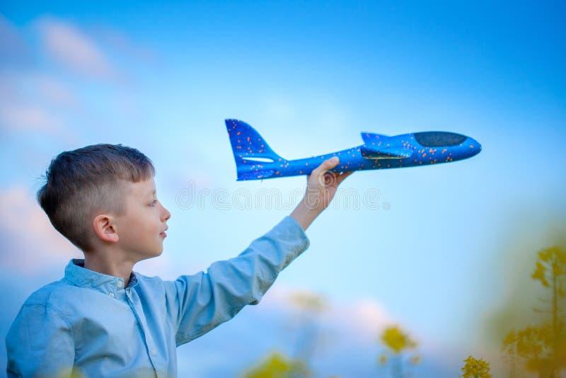 逗人喜爱的男孩使用与在旅行天空蔚蓝和梦想的一架玩具飞机  有蓝色玩具飞机的手 库存照片