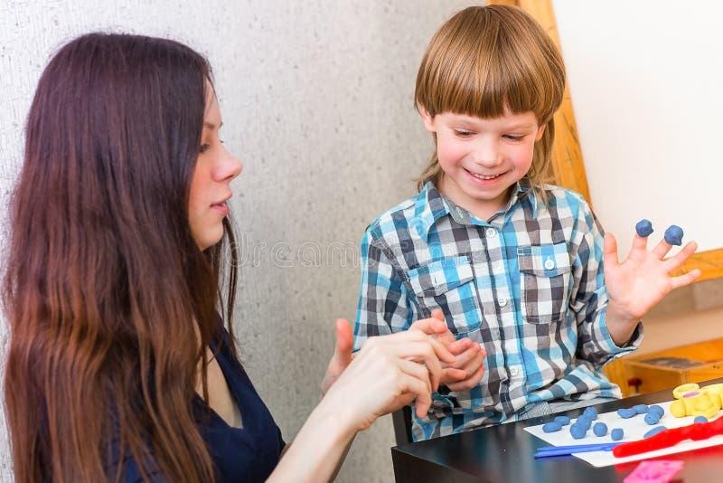 逗人喜爱的男孩和他的母亲一起演奏五颜六色的戏剧面团 在幸福家庭的消遣 库存照片