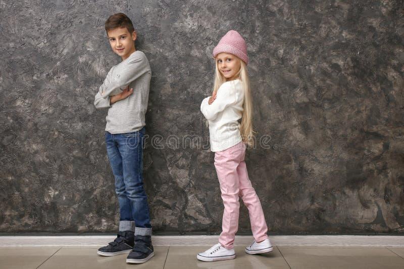 逗人喜爱的男孩和女孩时装的在灰色墙壁附近 免版税库存照片