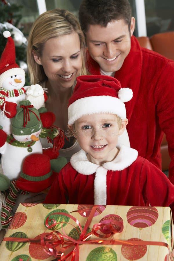 逗人喜爱的男孩在拿着与后边父母的圣诞老人成套装备礼物 库存照片