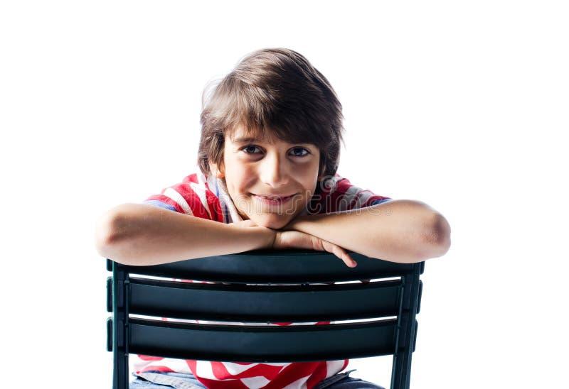 逗人喜爱的男孩坐微笑的椅子,隔绝 免版税图库摄影