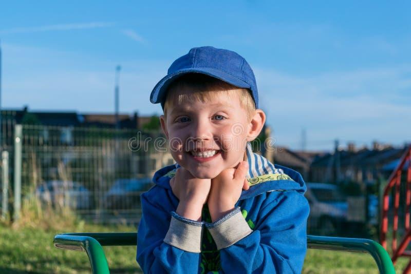 逗人喜爱的男孩坐操场,举行手在下巴附近,微笑和乐趣 免版税库存图片