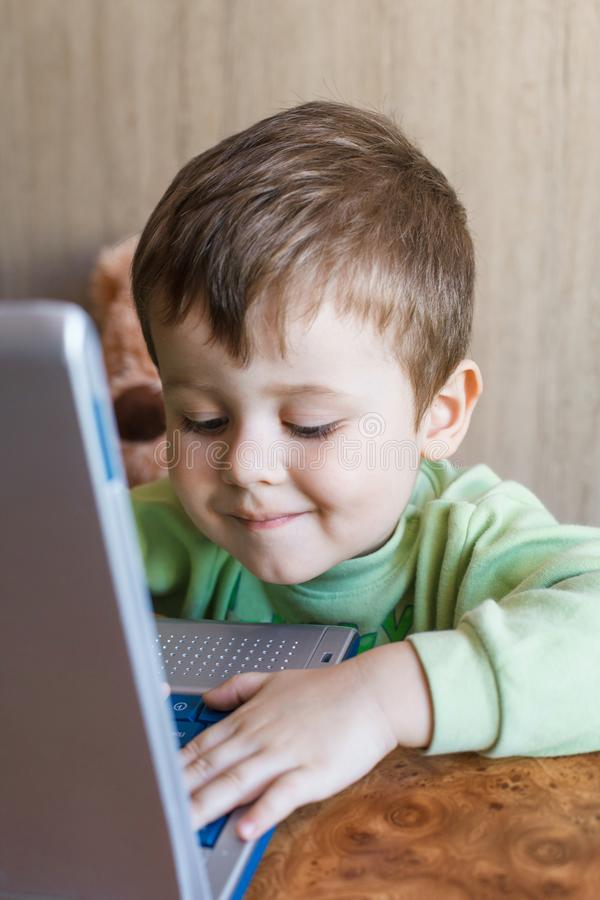 逗人喜爱的男孩推挤膝上型计算机键盘,并且他看屏幕 库存图片