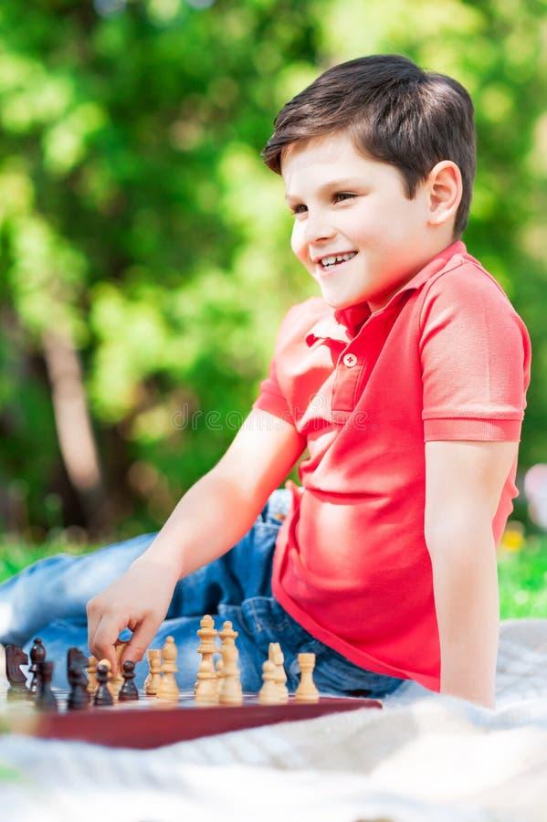 逗人喜爱的男孩是未来专业chessplayer 免版税图库摄影