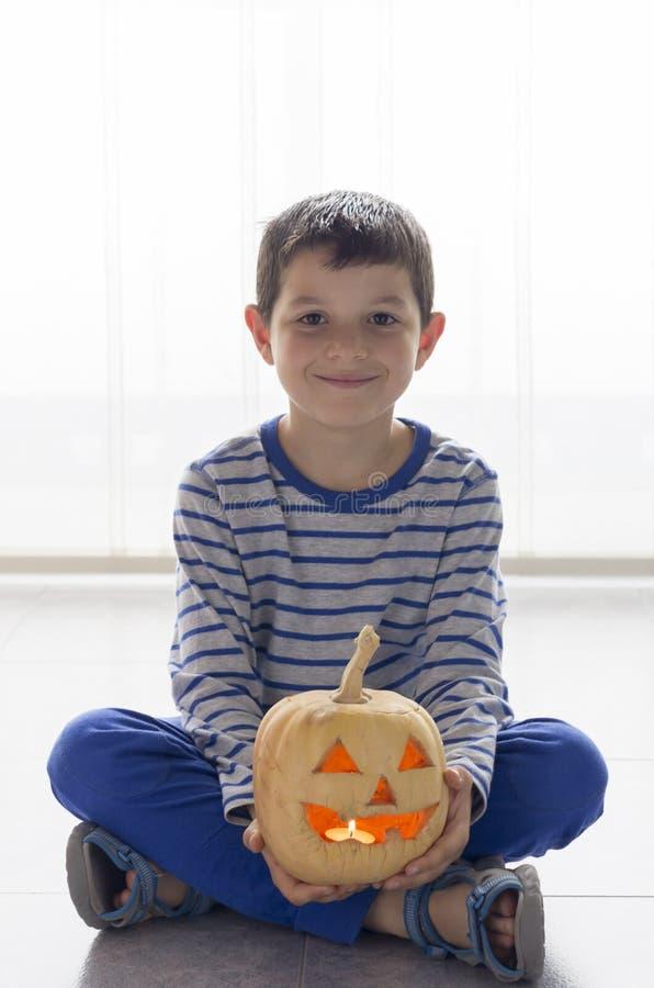 逗人喜爱的男孩用在万圣夜服装的南瓜在地板上 库存照片