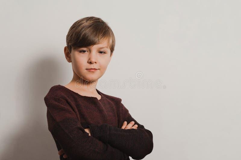 逗人喜爱的男孩画象有胳膊的在乳房,冷的神色横渡了 免版税图库摄影