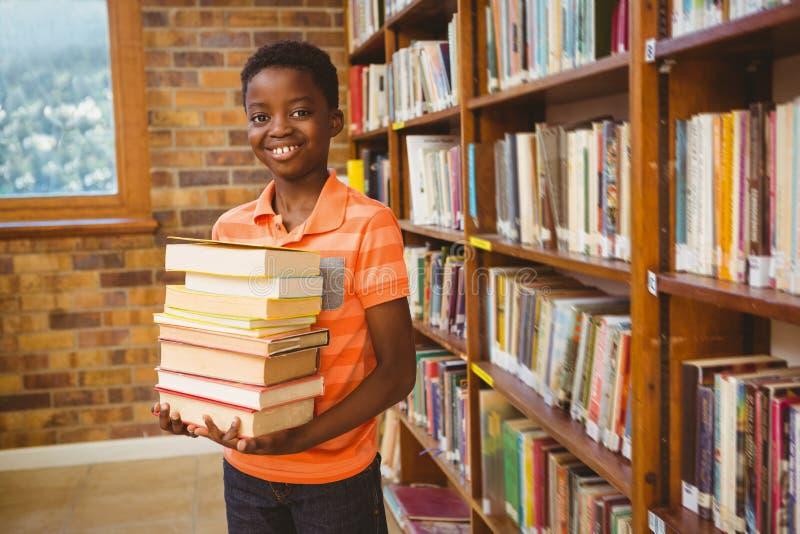 逗人喜爱的男孩运载的书画象在图书馆里 库存照片
