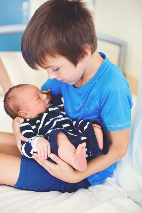 逗人喜爱的男孩,兄弟,第一次遇见他新的婴孩汤 免版税库存图片