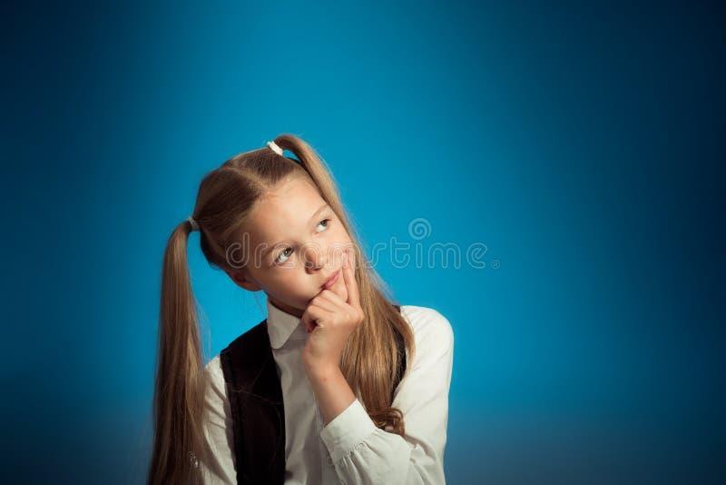 逗人喜爱的白种人女小学生考虑任务,投入手对她的面孔,看对边 库存照片
