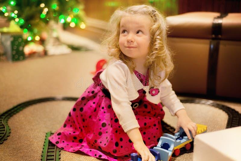 逗人喜爱的白种人白肤金发的卷发女孩使用与火车玩具室内在光迷离背景 免版税库存照片