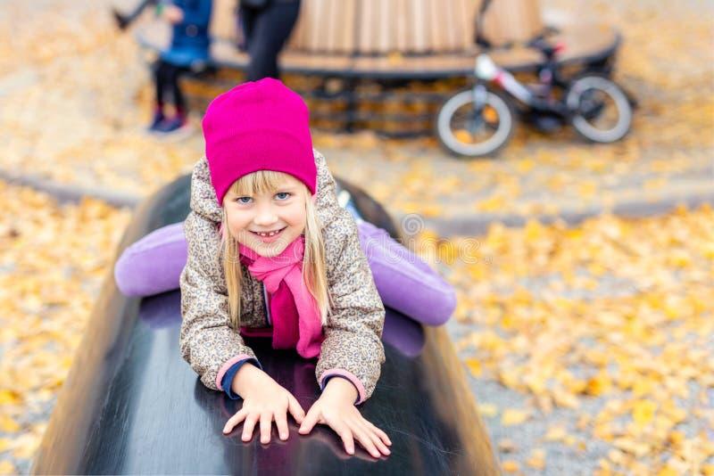 逗人喜爱的白种人白肤金发的女孩画象获得使用在现代室外操场的乐趣在城市公园在秋天 ?? 库存图片