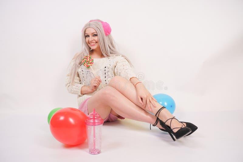 逗人喜爱的白肤金发的在乳状颜色被编织的毛线衣和滑稽的短裤打扮的白种人愉快的女孩,她坐单独白色地板与 图库摄影