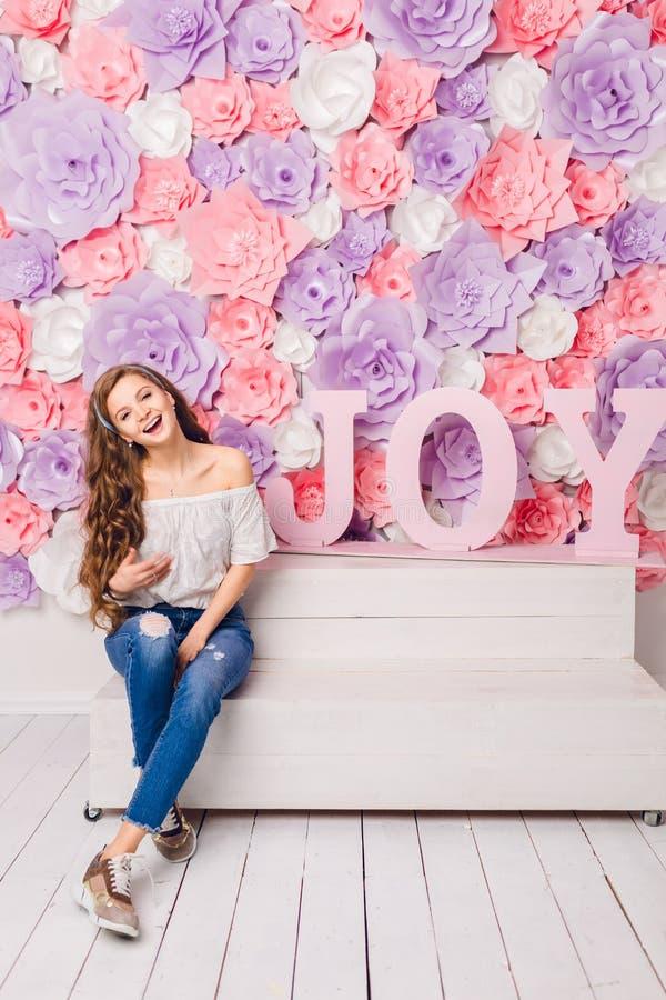 逗人喜爱的白肤金发的女孩坐一条长凳在广泛微笑的演播室 她有长的卷发并且佩带蓝色牛仔裤和白色t 免版税库存照片