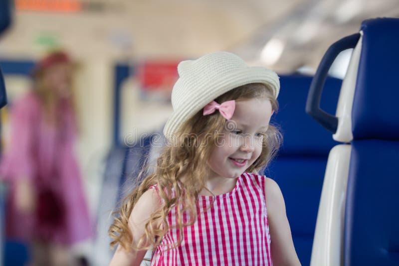 逗人喜爱的白肤金发的小女孩跑远离她的母亲在火车 免版税库存照片