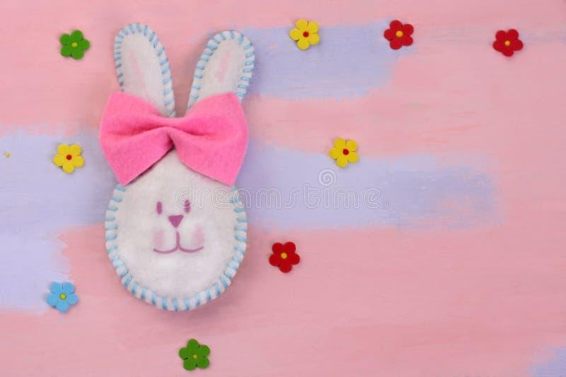 逗人喜爱的白色复活节兔子做了与一把桃红色弓的毛毡在与多彩多姿的花的桃红色蓝色背景 手工制造从毛毡 库存图片