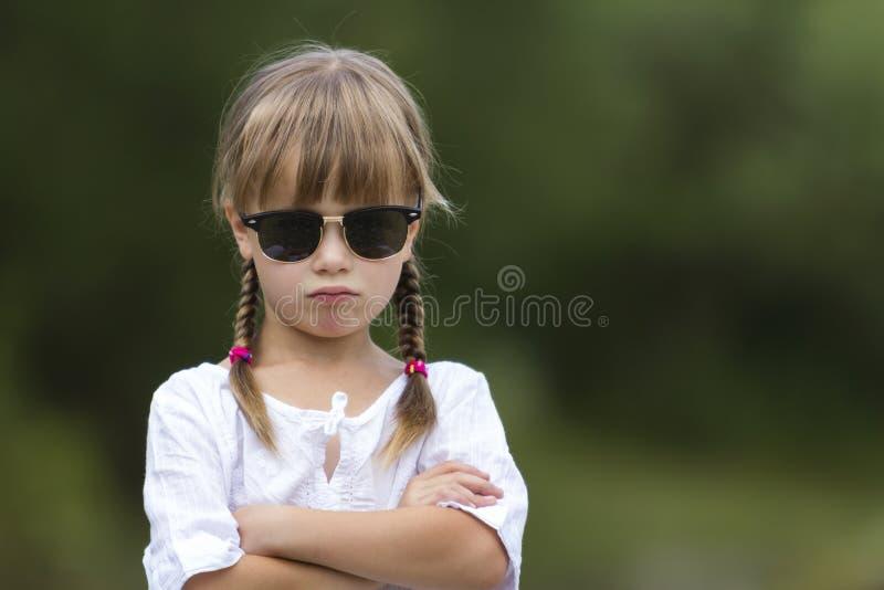 逗人喜爱的相当滑稽的女孩画象有白肤金发的辫子的在wh 免版税库存图片