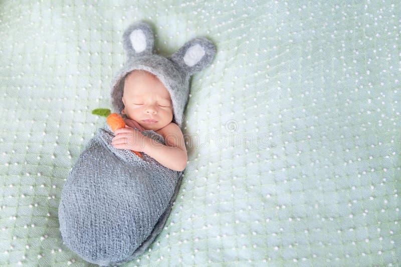 逗人喜爱的睡觉的新出生的婴孩穿戴了象复活节兔子 免版税库存照片