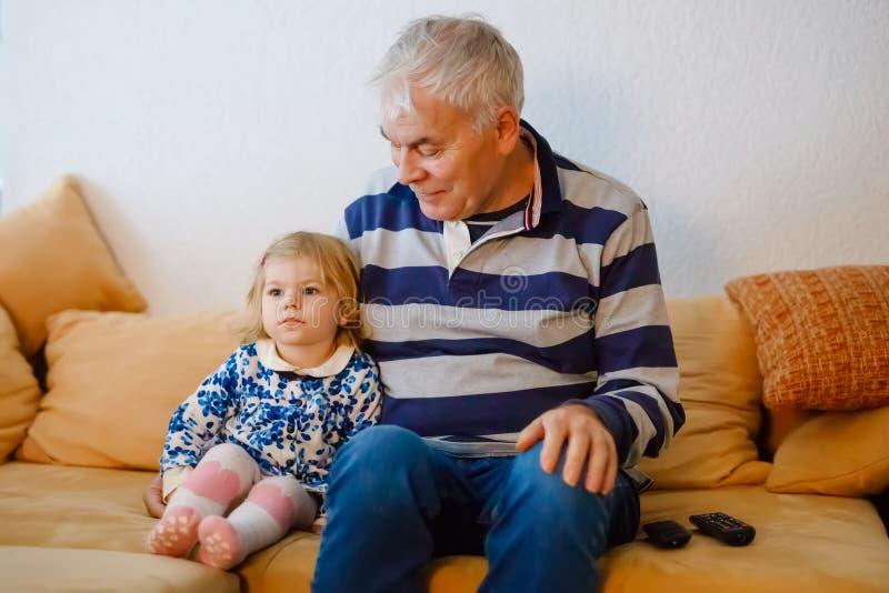 逗人喜爱的矮小的一起观看电视剧的小孩女孩和祖父 小孙女和愉快的退休的老人 库存图片