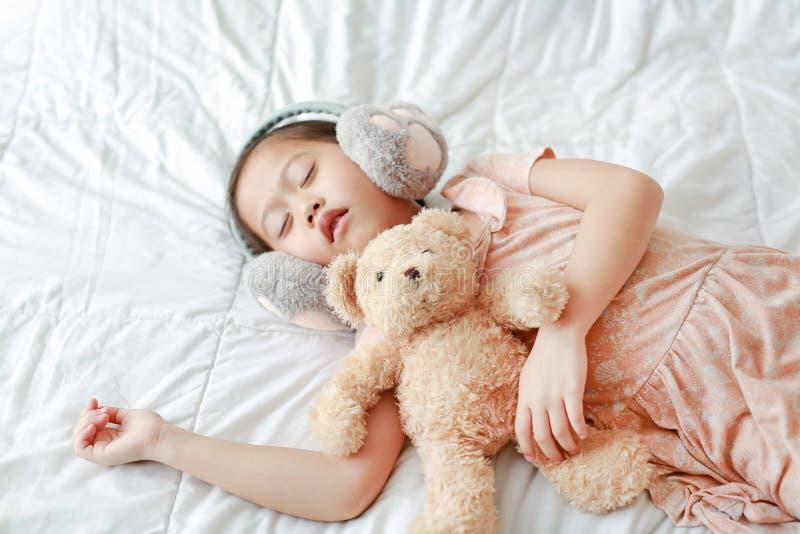逗人喜爱的矮小的亚裔与在家说谎在床上的玩具熊的女孩佩带的冬天耳朵笨拙的人 免版税图库摄影