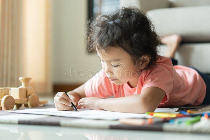 逗人喜爱的矮小的亚裔女孩画的家庭作业和写与颜色蜡笔在纸在她的家 免版税图库摄影