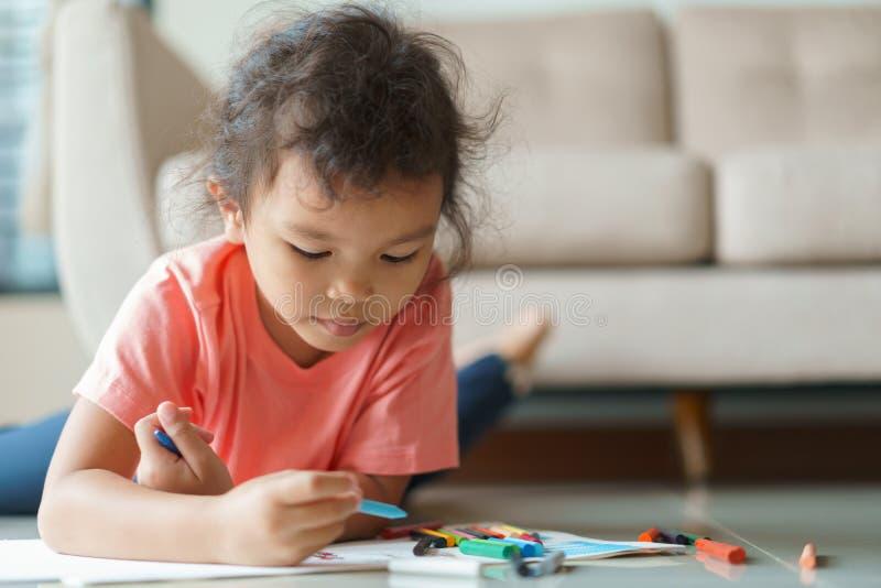 逗人喜爱的矮小的亚裔女孩画的家庭作业和在家写与颜色蜡笔在纸 免版税库存照片
