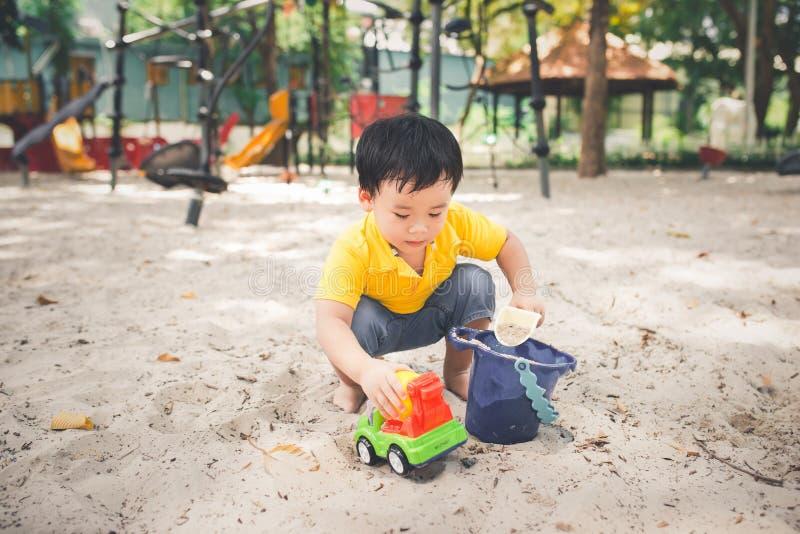 逗人喜爱的矮小的亚裔男孩在一个公园在户外一好天儿 免版税库存照片
