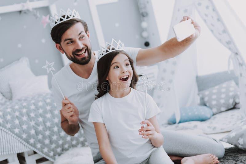 逗人喜爱的矮小的做Selfie的女儿和爸爸 库存照片