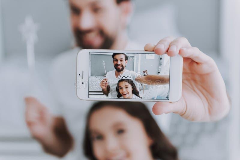 逗人喜爱的矮小的做Selfie的女儿和爸爸 库存图片
