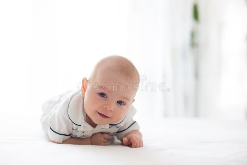 逗人喜爱的矮小的四个月的男婴,在家使用在床上 免版税图库摄影