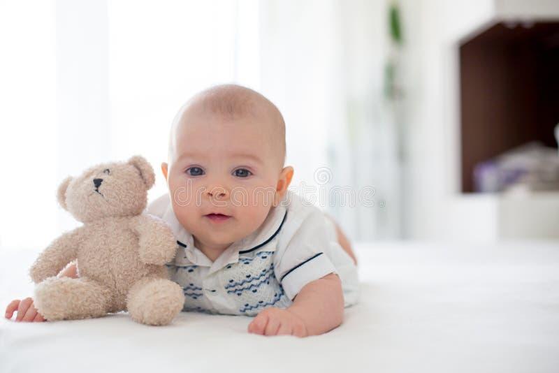 逗人喜爱的矮小的四个月的男婴,在家使用在床上 免版税库存照片