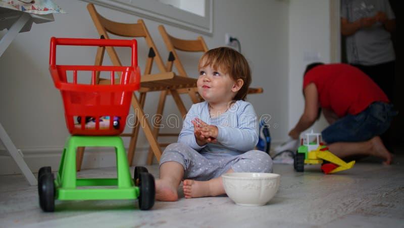 逗人喜爱的矮小的女婴坐硬木和微笑 免版税库存图片