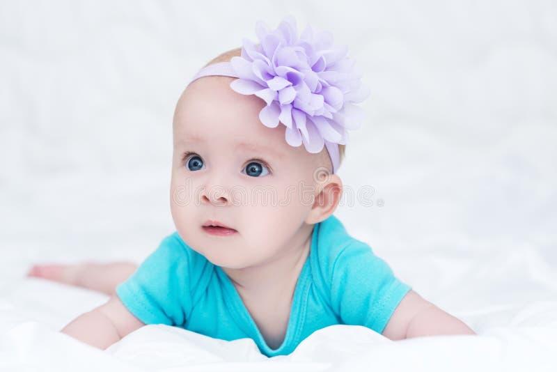 逗人喜爱的矮小的女婴画象有弓花的在她的头 库存照片