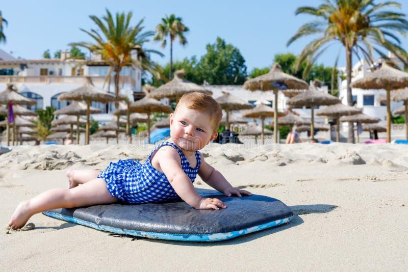 逗人喜爱的矮小的女婴画象游泳衣的在海滩在夏天 免版税库存图片