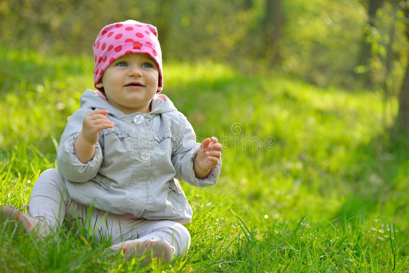逗人喜爱的矮小的女婴weared坐在绿草的一个桃红色帽子 库存照片