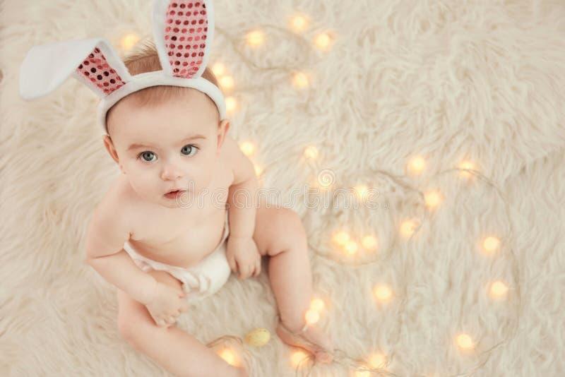 逗人喜爱的矮小的婴孩佩带的兔宝宝耳朵坐毛茸的地毯 免版税库存照片
