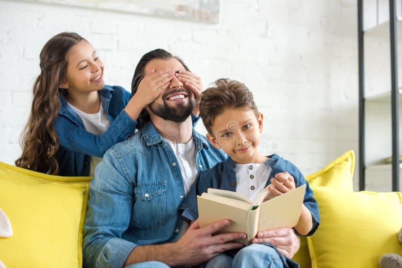 逗人喜爱的矮小的对愉快的父亲的女儿关闭的眼睛,当在沙发时的父亲和儿子看书 库存图片